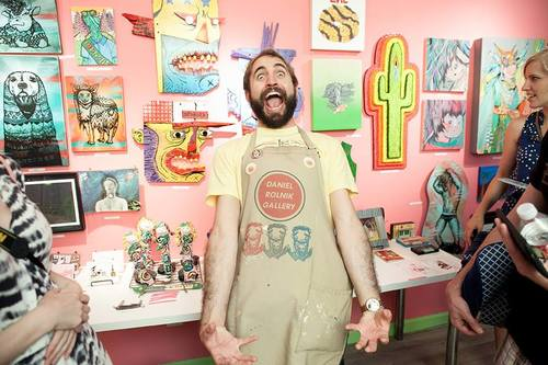 """Daniel Rolnik (c) wearing the apron at the opening reception of """"Girl Scouts & Adventure Guides"""" (Aug 2015) - with male nipple stickers by Micol Hebron."""