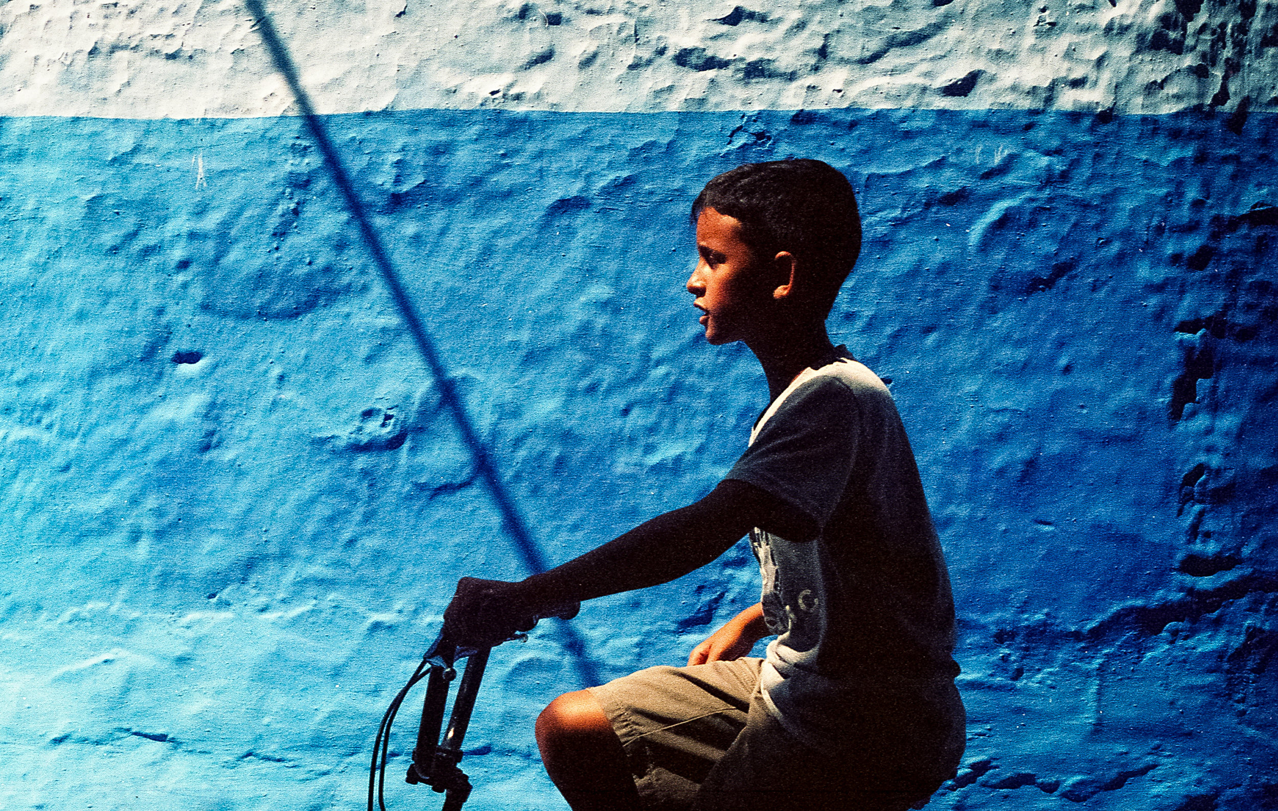 Boy riding a bike in the streets of Chefchaouen, Morocco. Summer 2017 (Portra 400)
