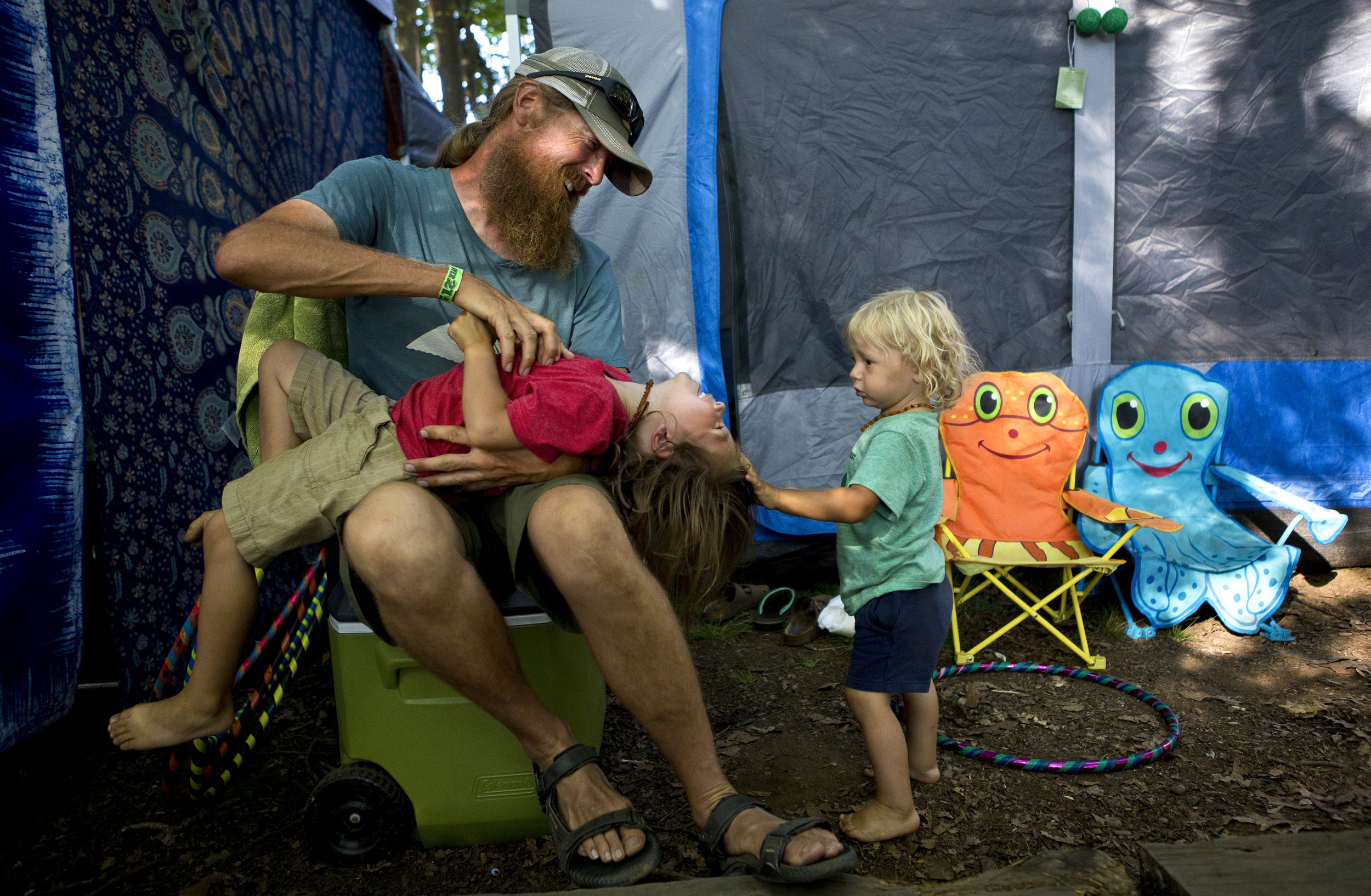 Rob Propster, 47, tickles his son Leo Propster, 4, while Sawyer Propster, 2, watches at their campsite during FloydFest in Floyd, Va. on July 28, 2018.