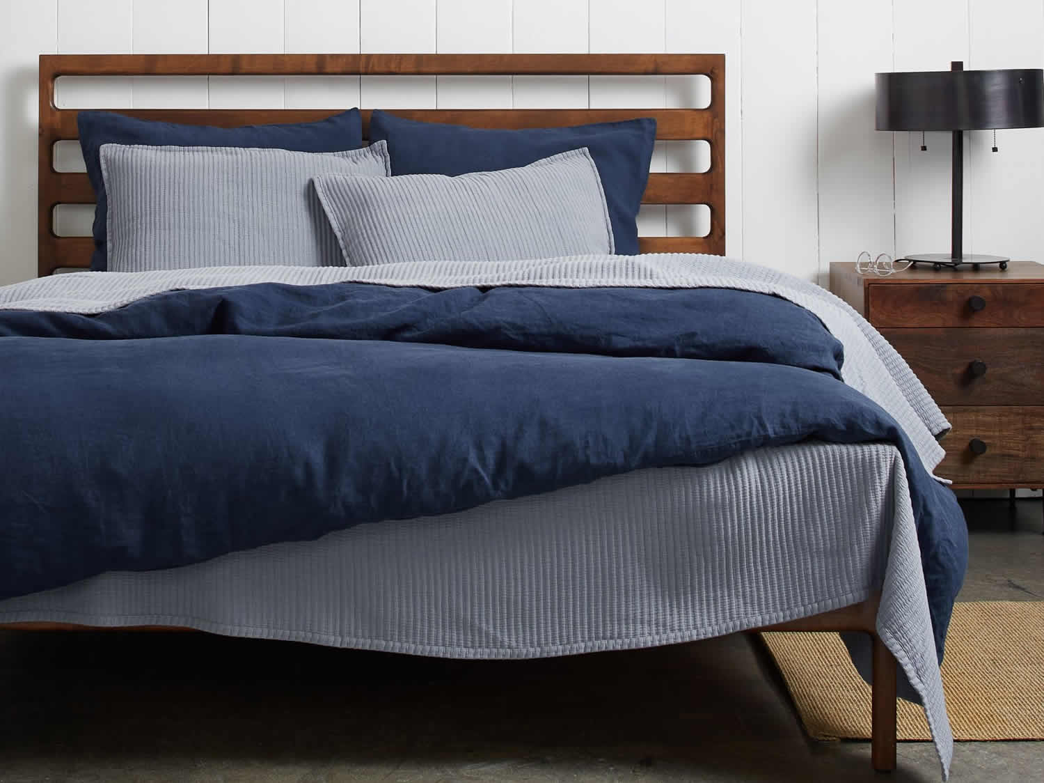Storm Blue Coverlet  by Parachute being used under a quilt as a light-weight blanket