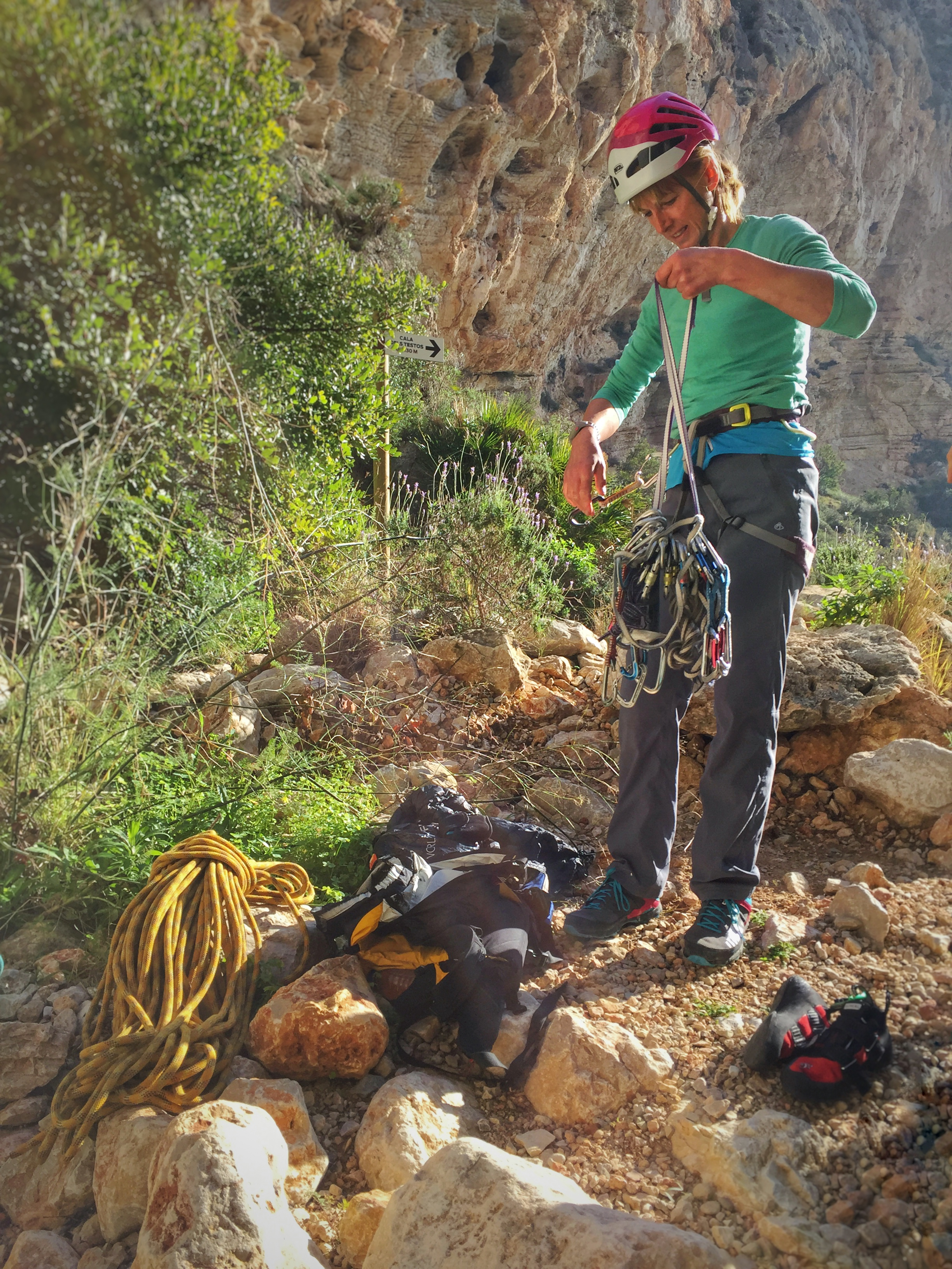 Kate gearing up at the base of multipitch sea cliff climb Sonjanikka at Morro Falqui, Costa Blanca
