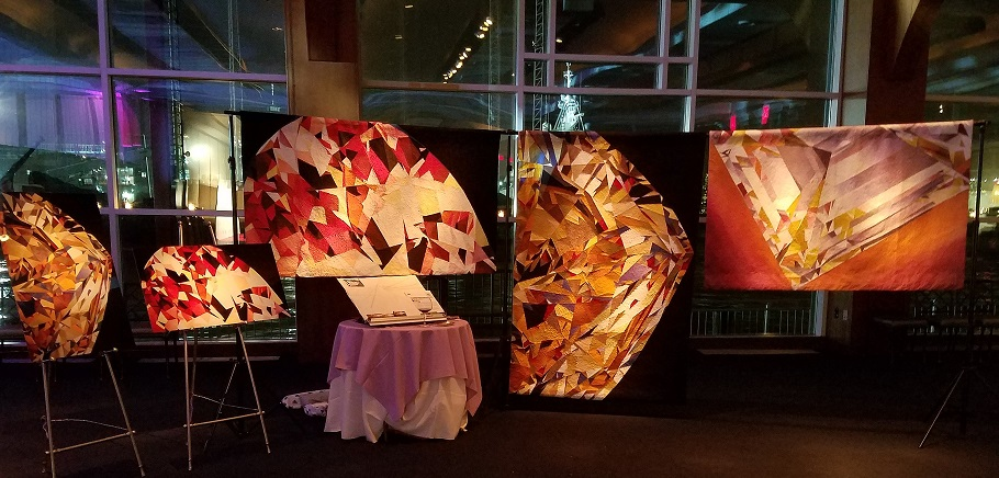 gemstone quilt artwork display at WJA exhibit in New York City at night