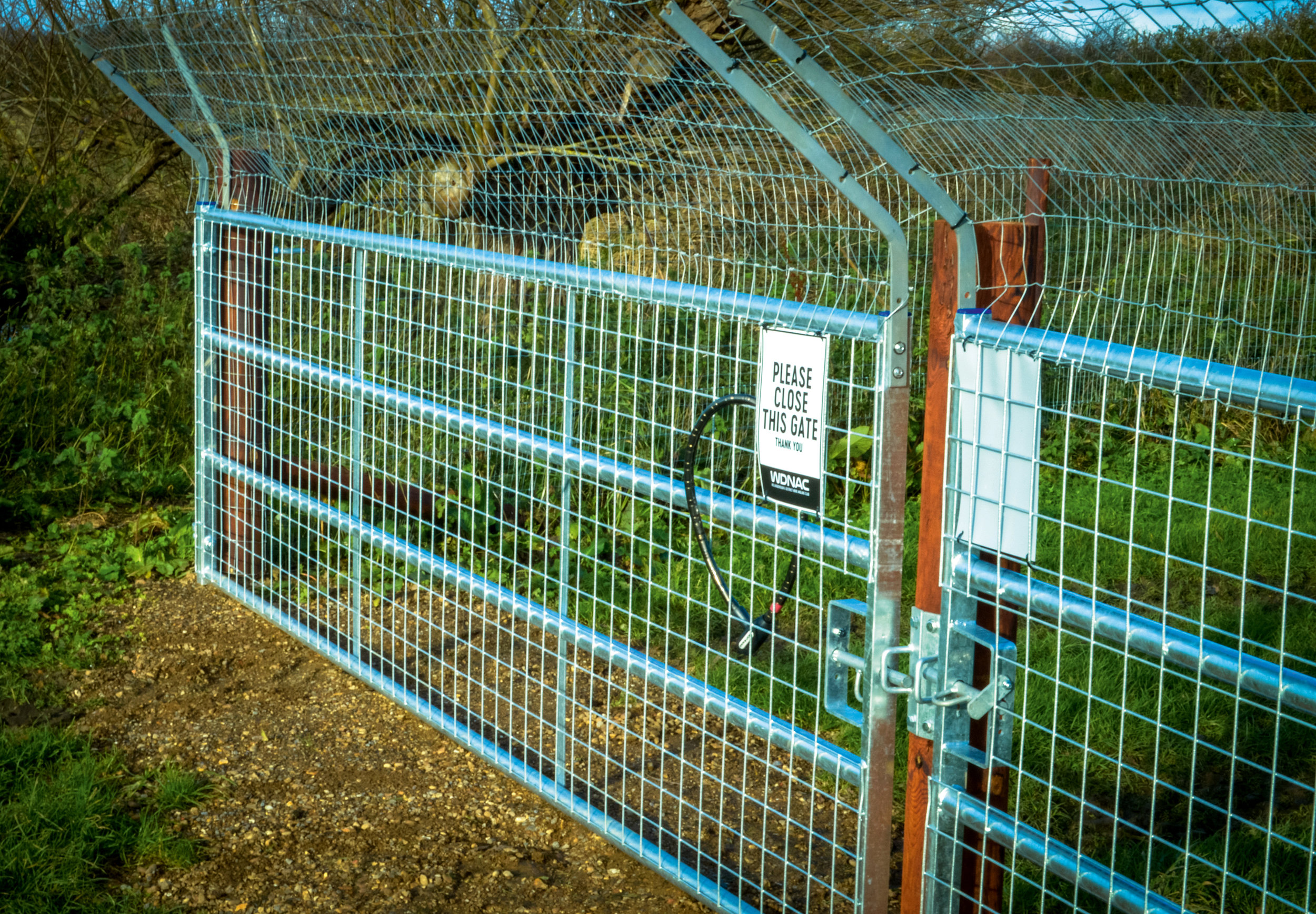 Vehicle and pedestrian gates, including a buried telegraph pole and a gravelled area to prevent burrowing