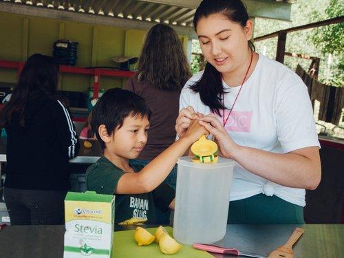 Annika helping summer camper make lemonade.