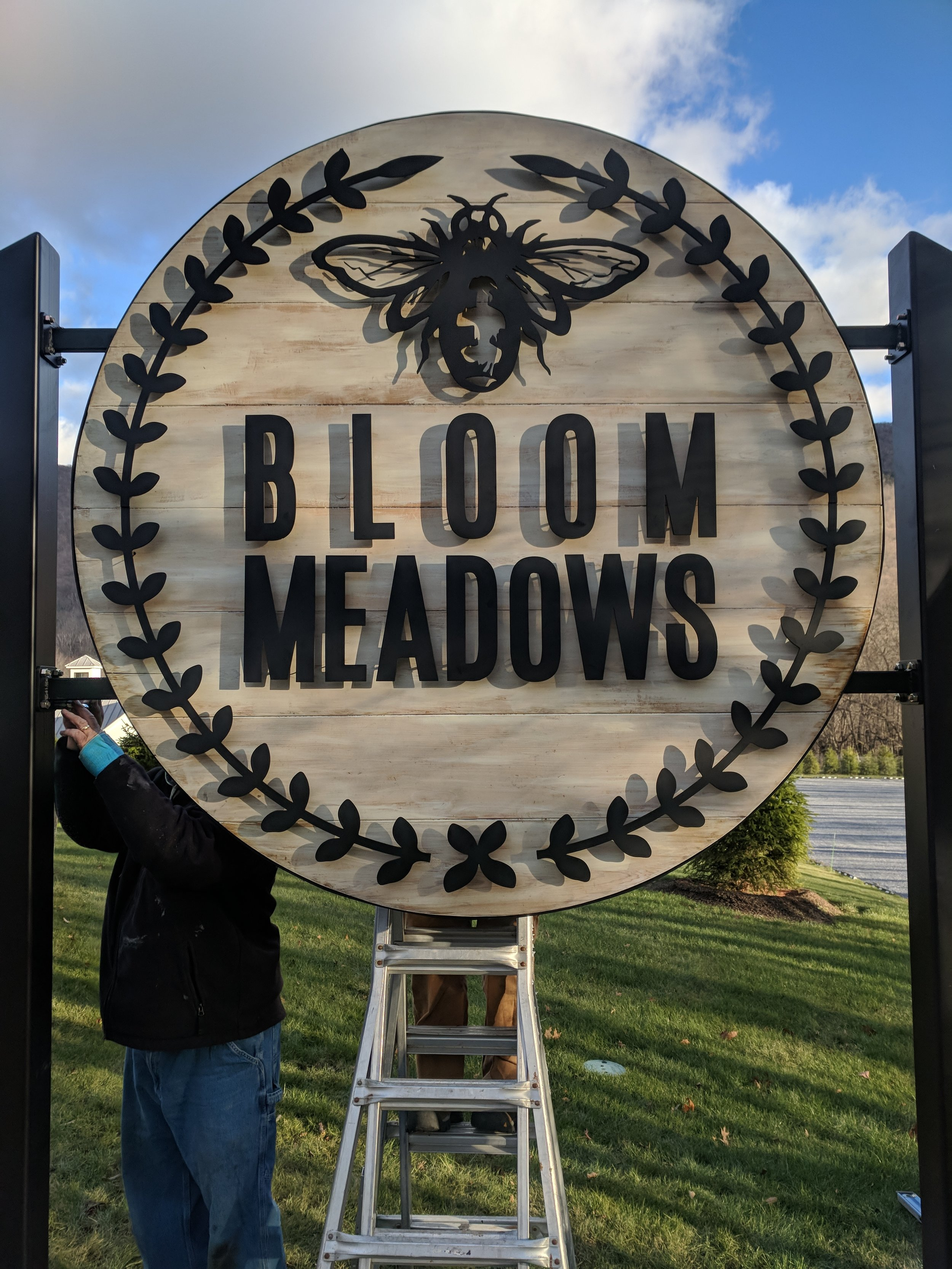 6ft Cedar Sign white washed w/ black powder coated 11GA steel letters. Custom bracket and posts