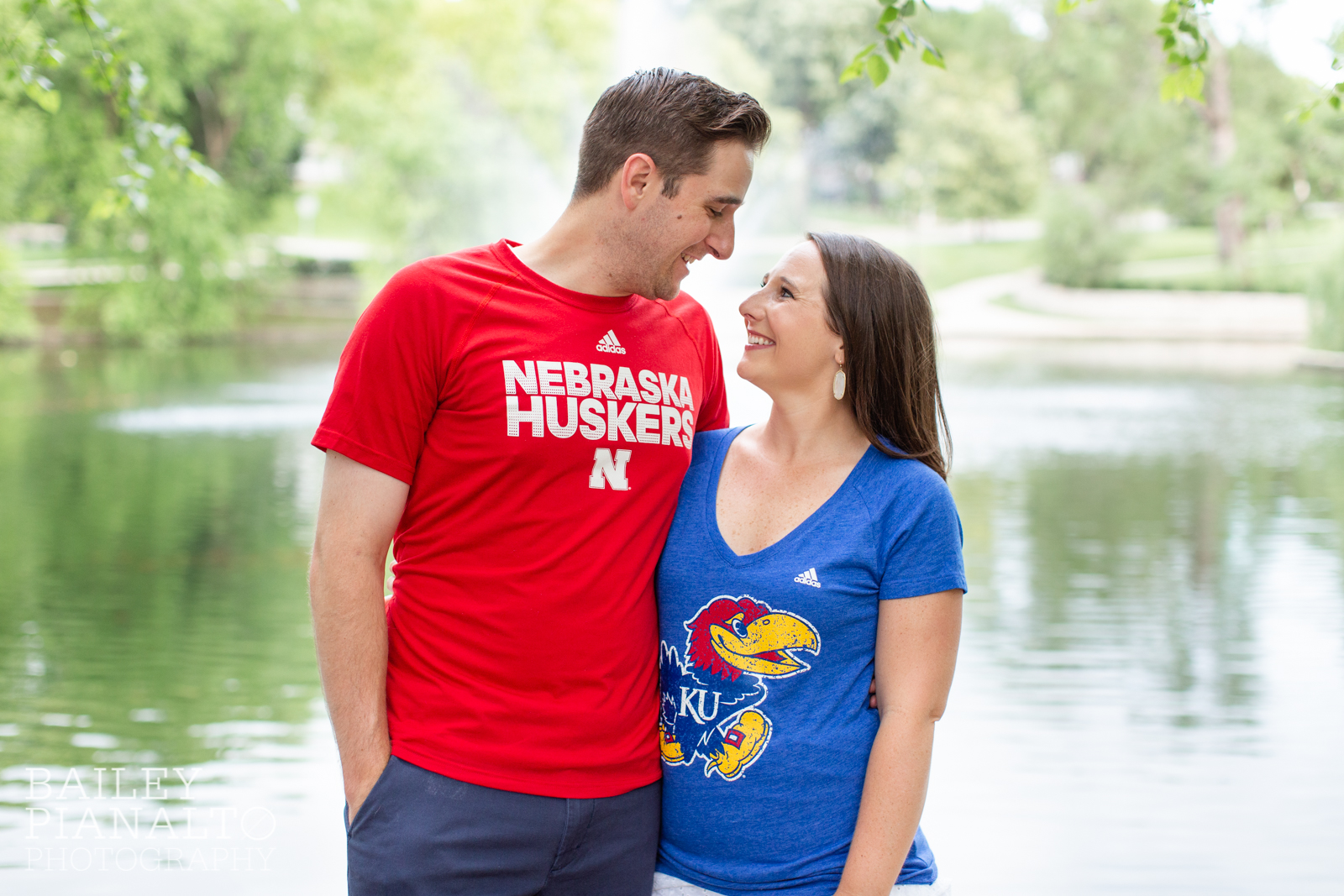Nebraska Husker and Kansas Jayhawk T-Shirts in Colorful Sunset and Skyline Engagement Session Inspiration Loose Park | Kansas City, MO