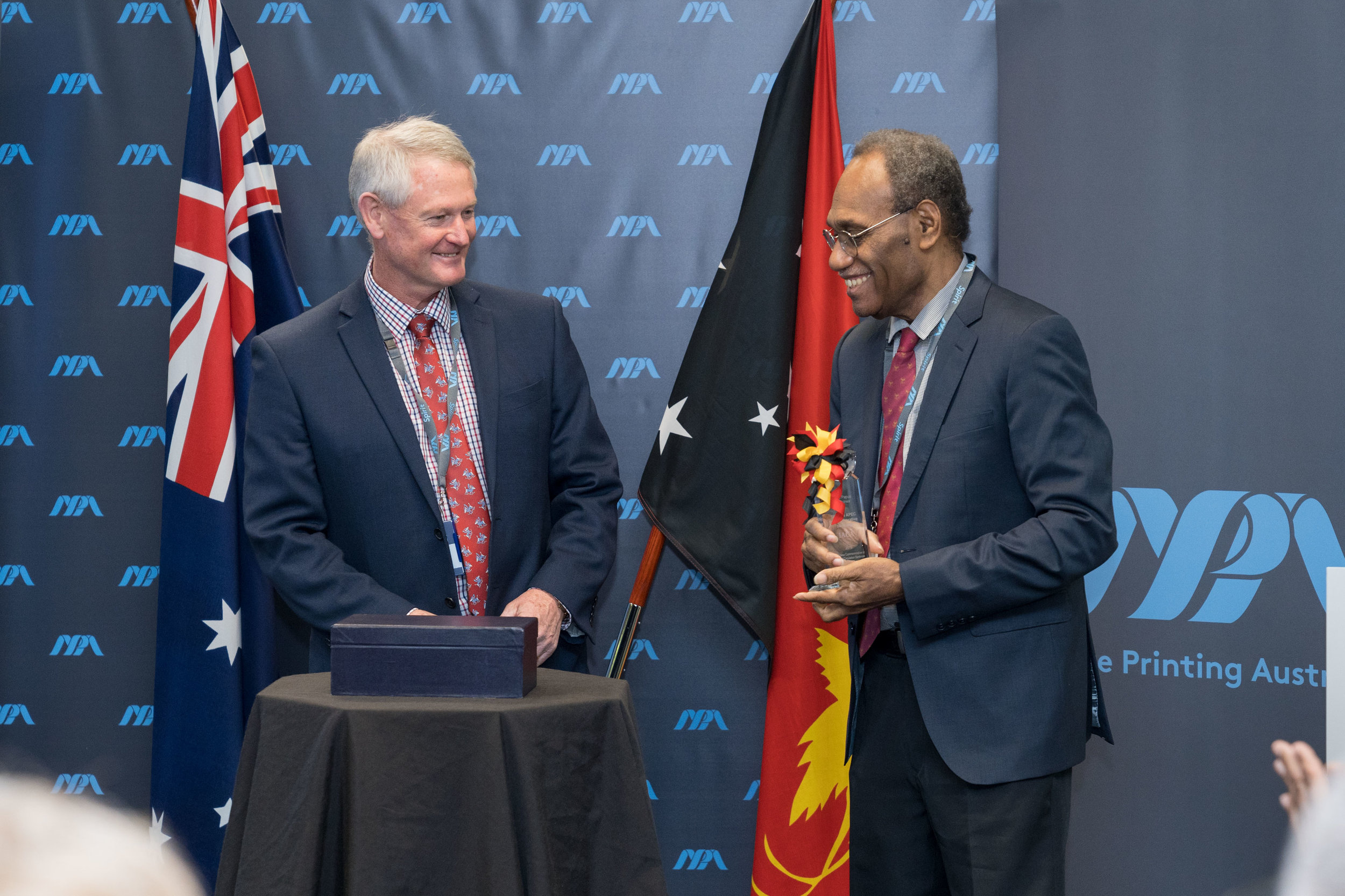 NPA CEO Malcolm McDowell officially presents the IACA Award for Excellence to BPNG Deputy Governor Joe Teria after the nation's new K100 note was recognised as a Finalist for the Best New Commemorative or Limited Circulation Banknote