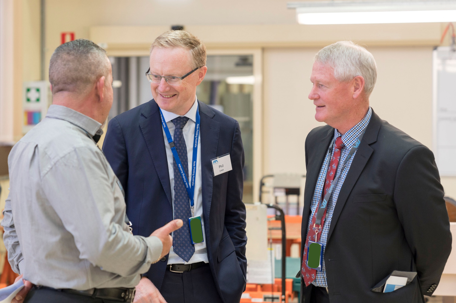 RBA Governor Phillip Lowe chats with NPA Passports Production Manager Roy De Freitas as CEO Malcolm McDowell looks on.