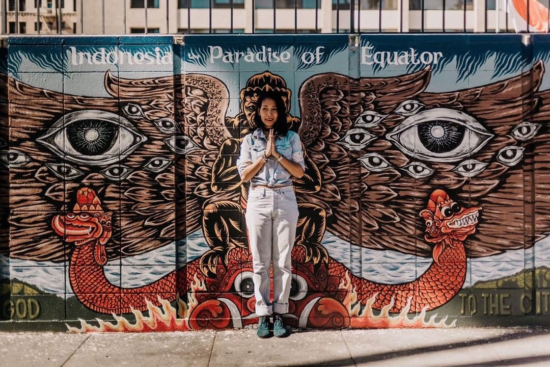 """Lolo Santosa is the founder of Toko-Toko, a Los Angeles-based boutique that celebrates sustainable, fair trade, vegan products from Indonesia. Toko-Toko is an Indonesian term for the English plural """"shops."""" She's standing in front of the Consulate General of Indonesia - LA. The mural is by @bangkit.arise. Photo Credit: @wanderlustcreatives."""