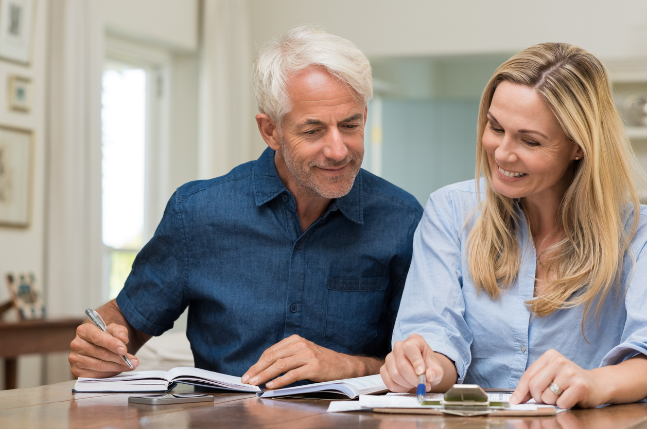 50 to 60 year old couple filling out paperwork
