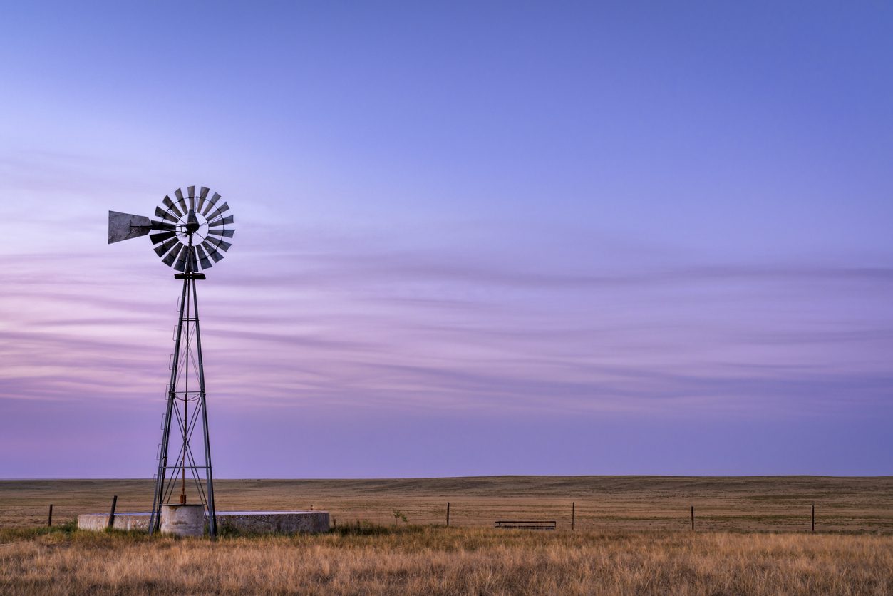 windmill at sunrise in rural america