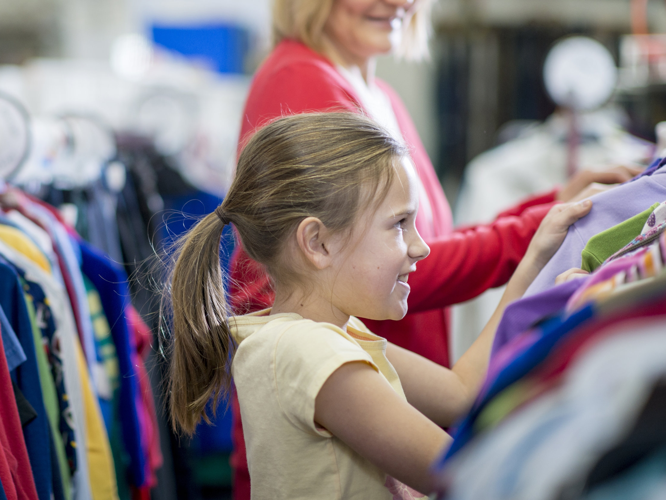 little-girl-looking-at-clothes-in-the-store-picture-id508406864.jpg