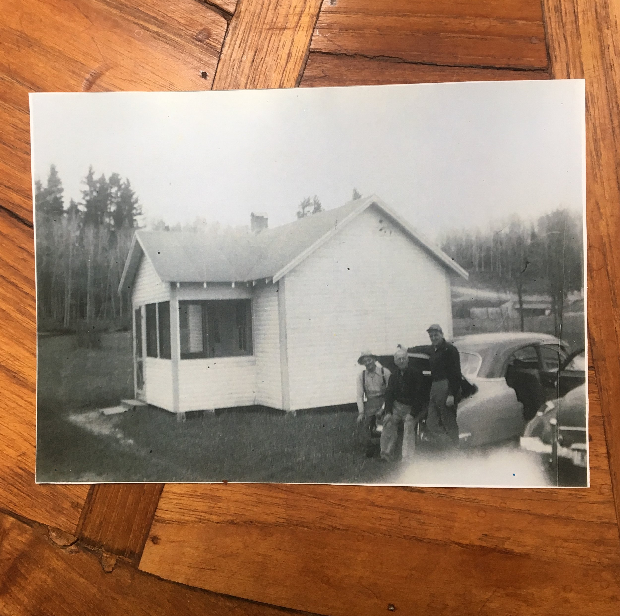 A Cabin on the Flats - This cabin once stood on The Flats, where the current resort owner's Red House stands today. Mc Masters Bridge is in the background. Denny stayed in these cabins in the late 1940's, when he was about 10 years old. Pictured left to right are then-owner Norman McCabe, Denny's grandfather Jack who passed in 1951 and a third person, unknown.
