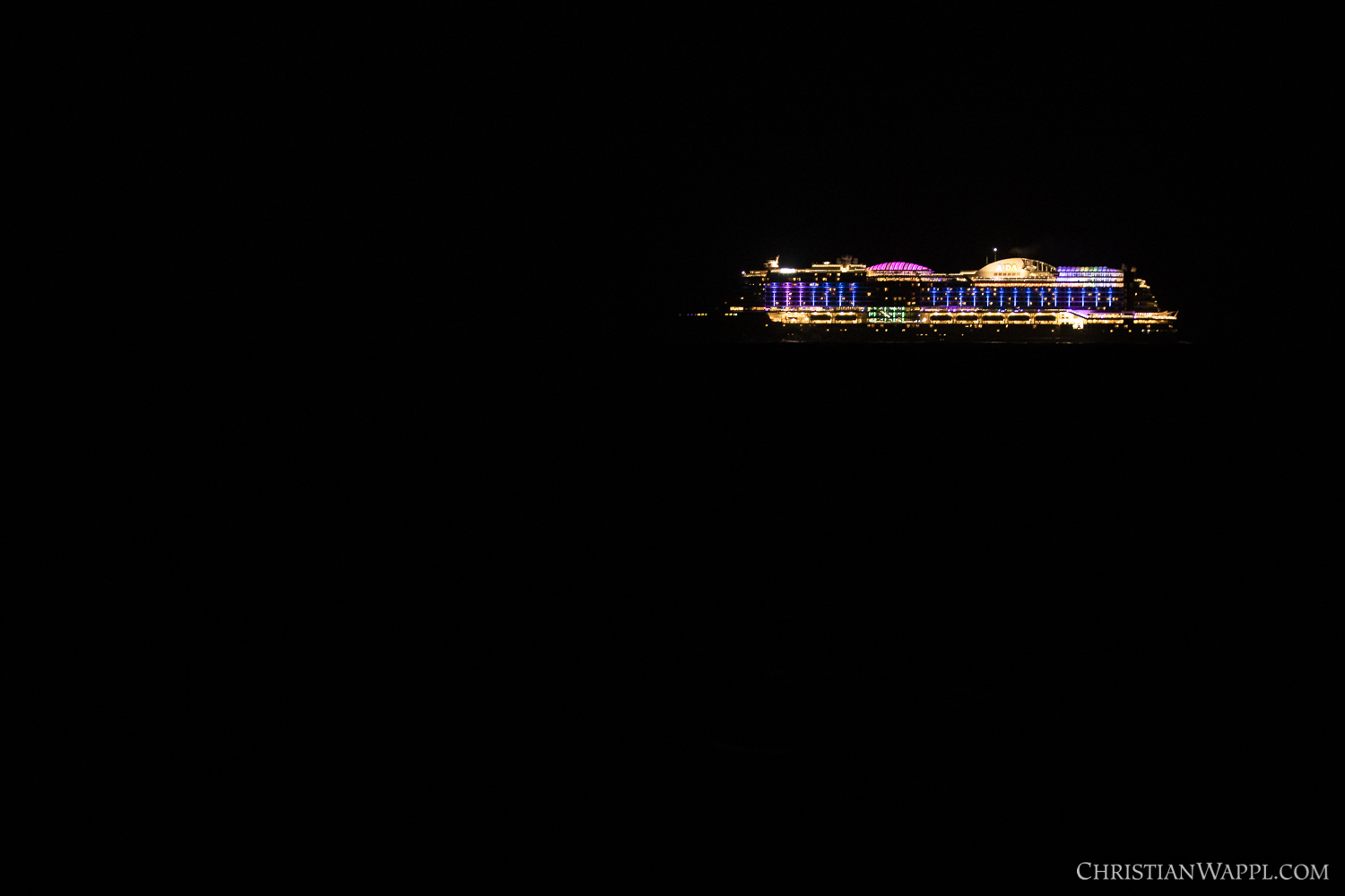 A cruise ship, cleverly combining light pollution with regular pollution