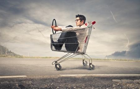 22776331 - businessman into a cart pretending to drive a car