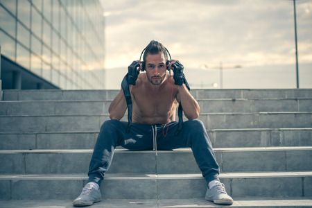 42832503 - getting motivated for hard workout, listening to the music with headphones on and gloves for trainning. selective focus