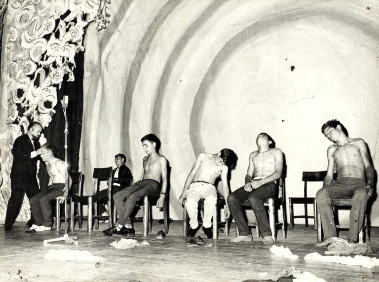 A hypnotist entrances several young men onstage, mid-20th century