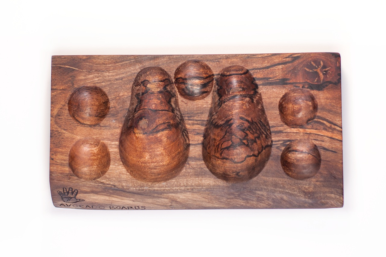 """Avocado Boards - Hand-carved serving boards made to present the avocado """"on the half-shell,"""" removed from its skin, in a deconstructed salad format, alongside condiment wells with which the diner can customize their meal. Hewn from avocado wood (2015) and Maine maple (2016) in small batches, and featured at the California Avocado Festival in those same years."""