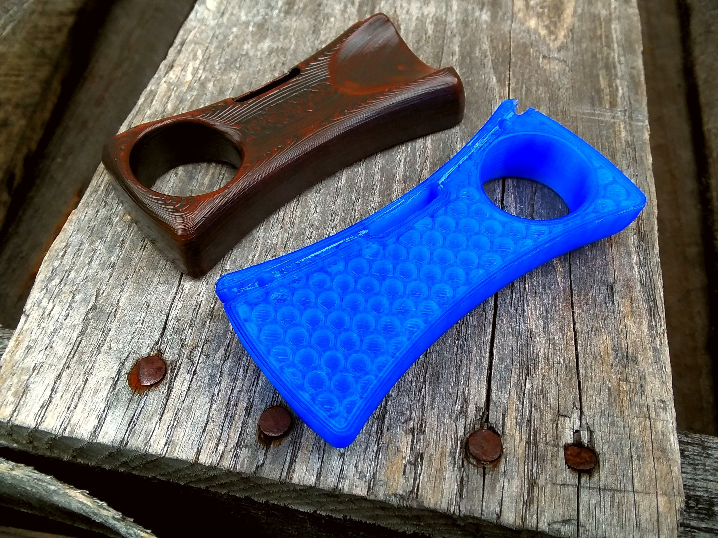 Our Weaver slingshot shown here in translucent blue (near) and graphite over copper (far)