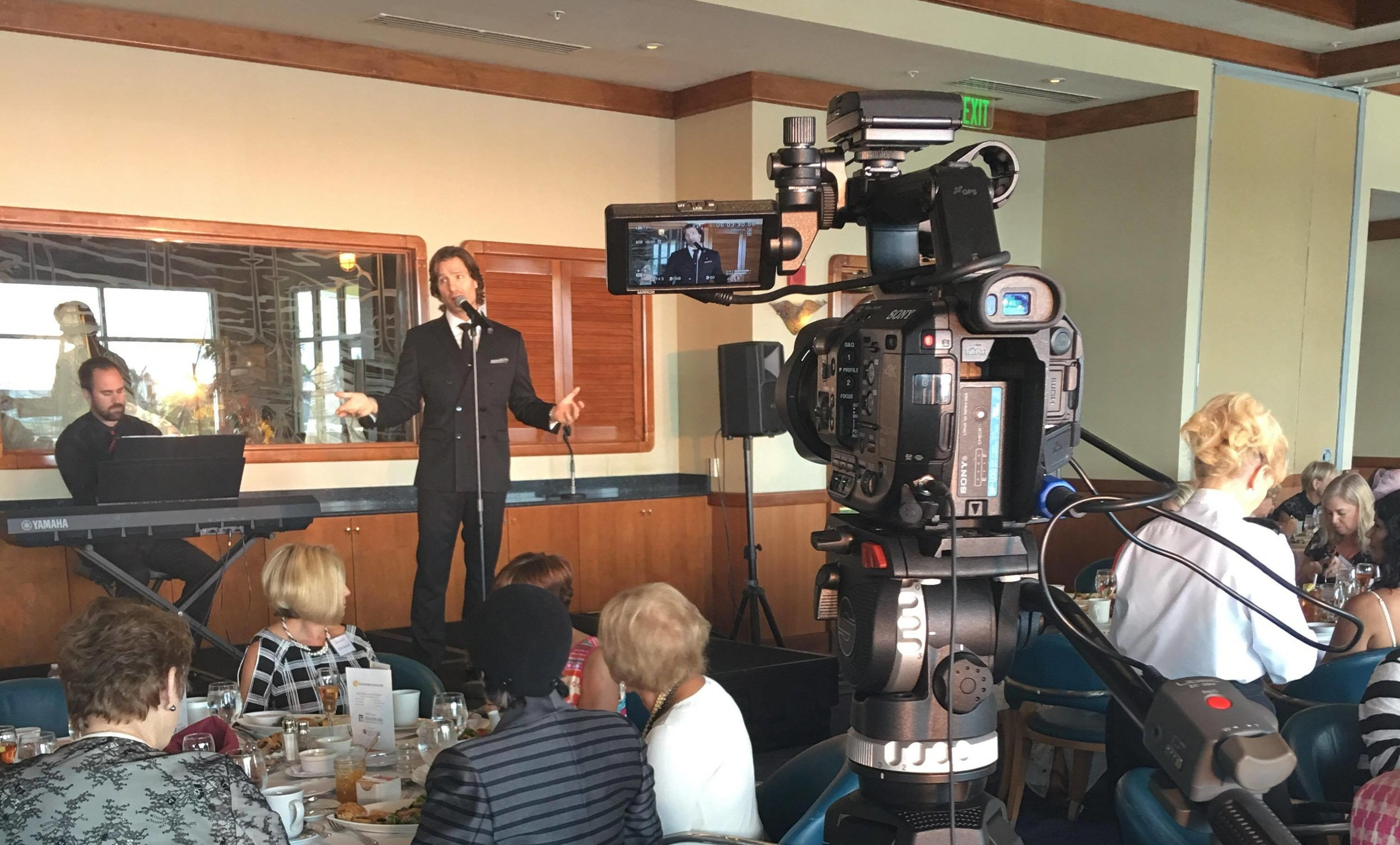 John Cudia singing on stage at the Naples Sailing & Yacht Club