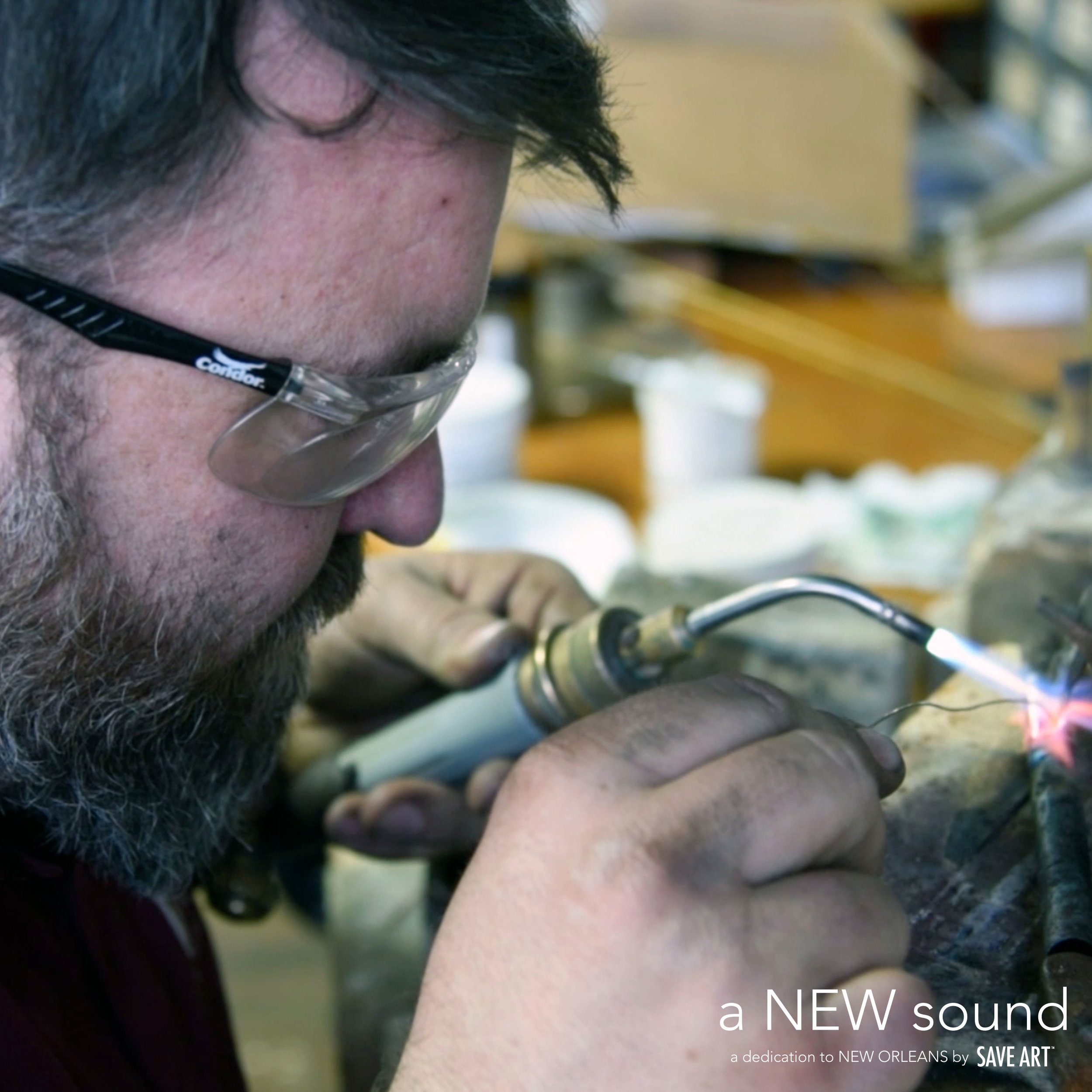 Above:  Mike Corrigan welding chicken ornament onto trumpet.