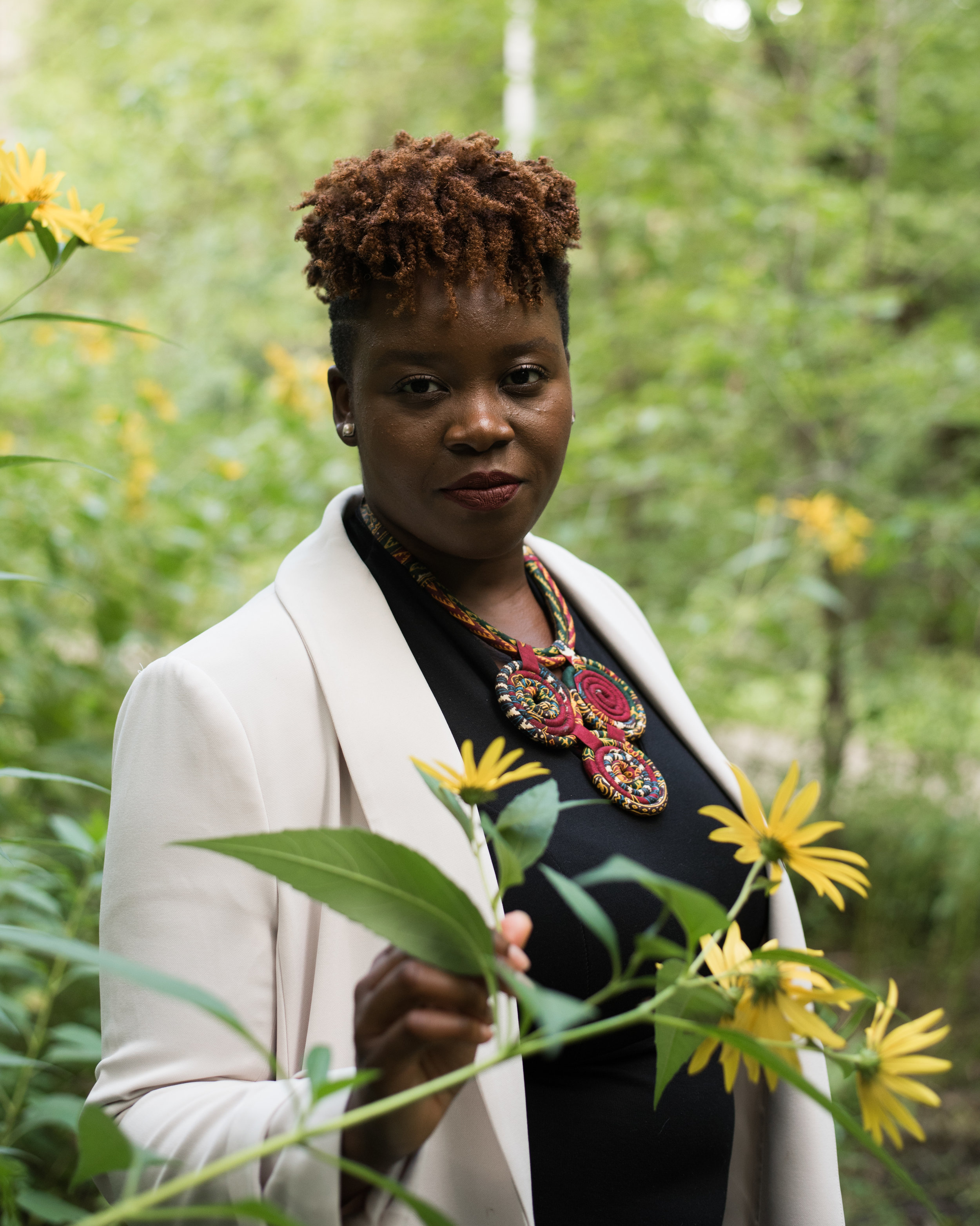 Image Description: Yamikani holding yellow flower with forest in the background. Yamikani is wearing black dress with white jacket &red necklace.  Photo by Jessica Laforet