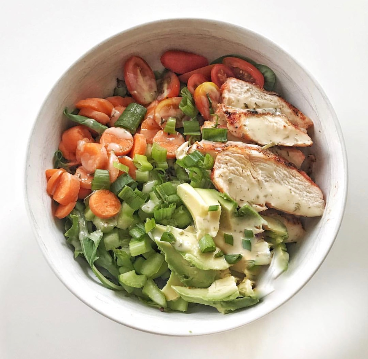 Buffalo Chicken Salad  Protein: Grilled chicken brushed with Frank's Red Hot Sauce Vegetables: Spinach, spring mix, celery, carrots, tomatoes, avocado Toppings: Green onions, Primal Kitchen ranch dressing