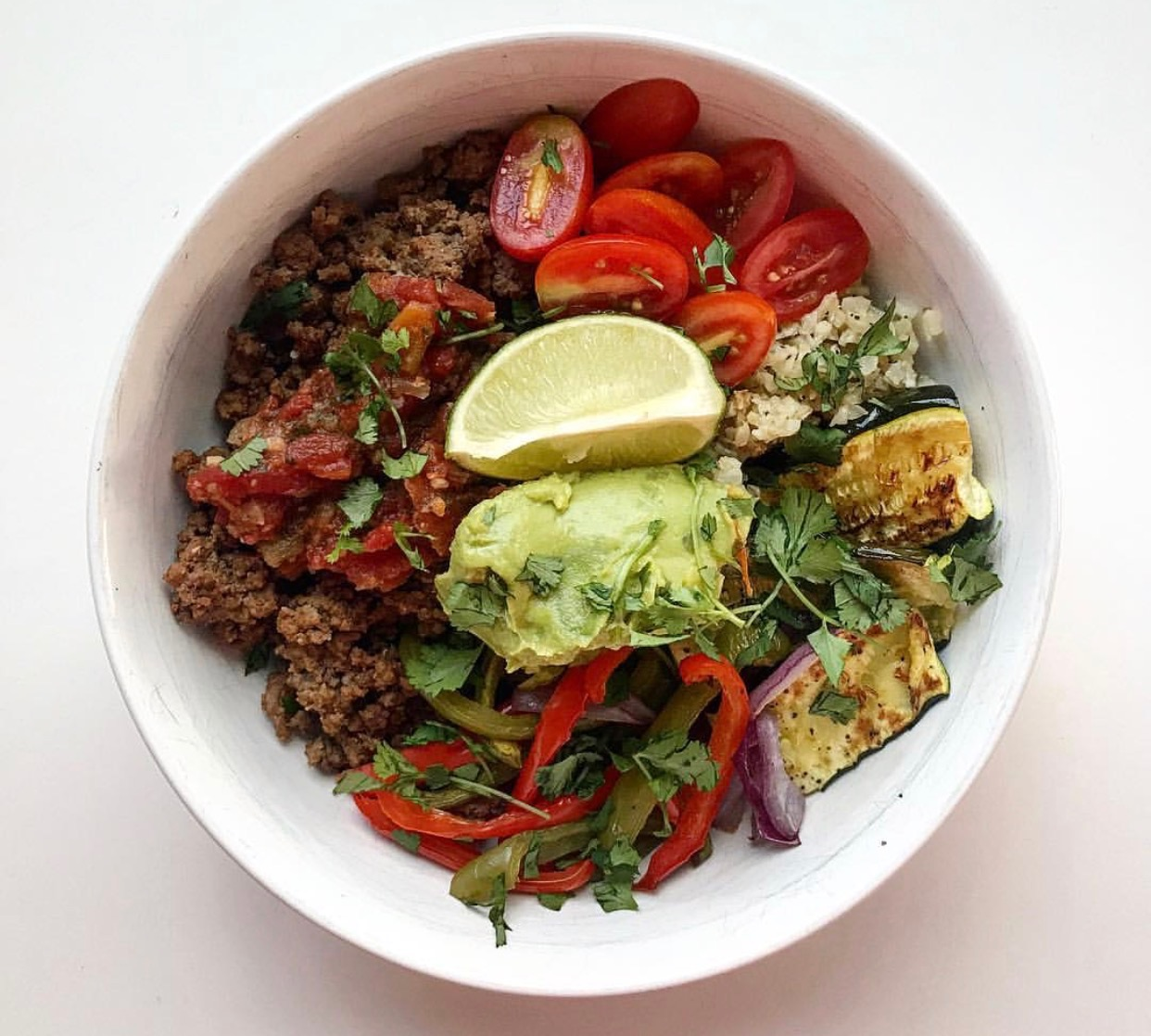 """Taco Bowl  Protein: Grass fed ground beef with taco seasoning Vegetables: Red onion, bell pepper, zucchini, cauliflower """"rice"""", grape tomatoes Topping: Salsa, guacamole, cilantro, lime"""