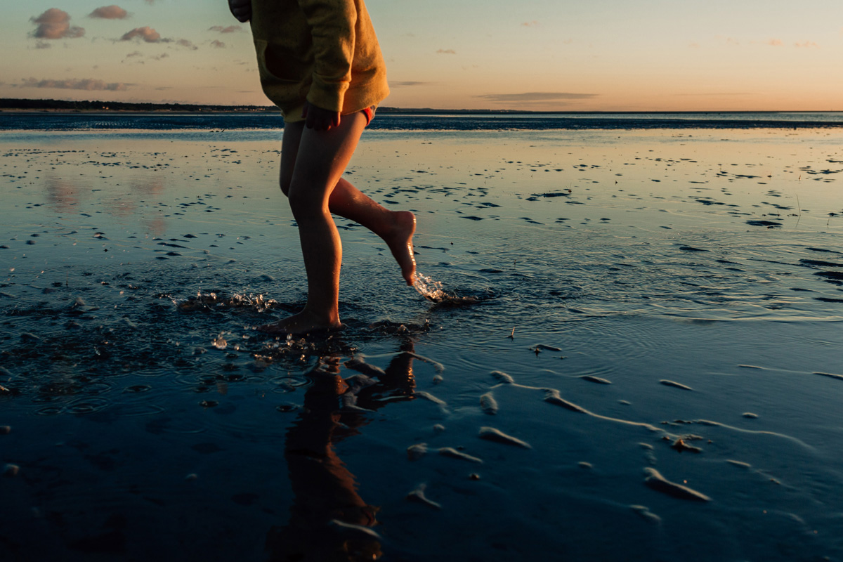 boy at skaket low tide by laura barr photography