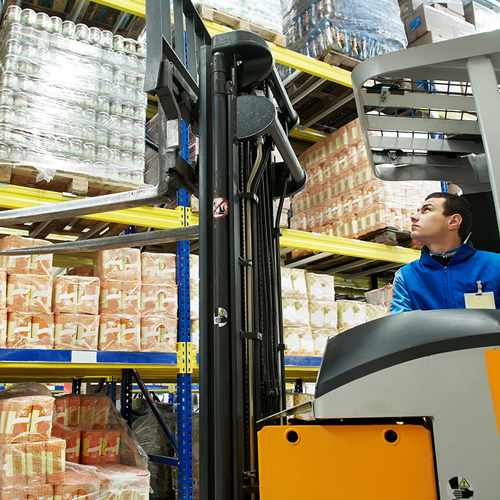 Man on forklift picking skids of stretch wrapped products off warehouse shelf.