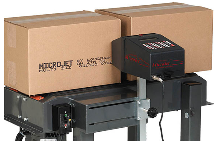 An industrial ink jet printer coding boxes as they move along a conveyor.