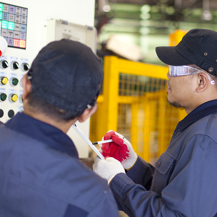 Two Service Technicians fixing a used packaging machine.