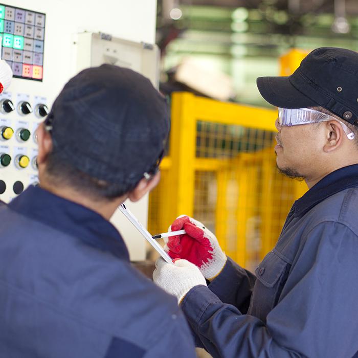 Two Packaging Equipment Service Technicians Fixing Machine