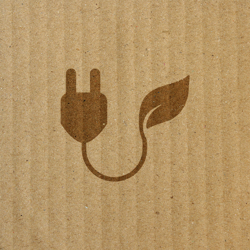 plug with leaf icon on top of cardboard texture background
