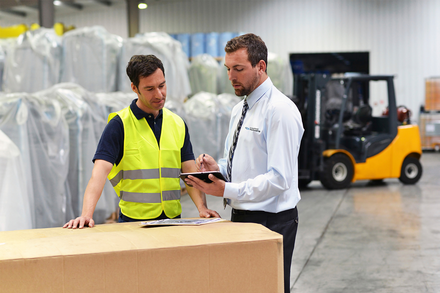 man in reflective yellow vest standing next to man with clipboard in warehousing facility