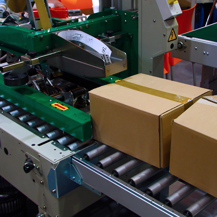 two cardboard boxes on conveyor attached to green case sealing machine