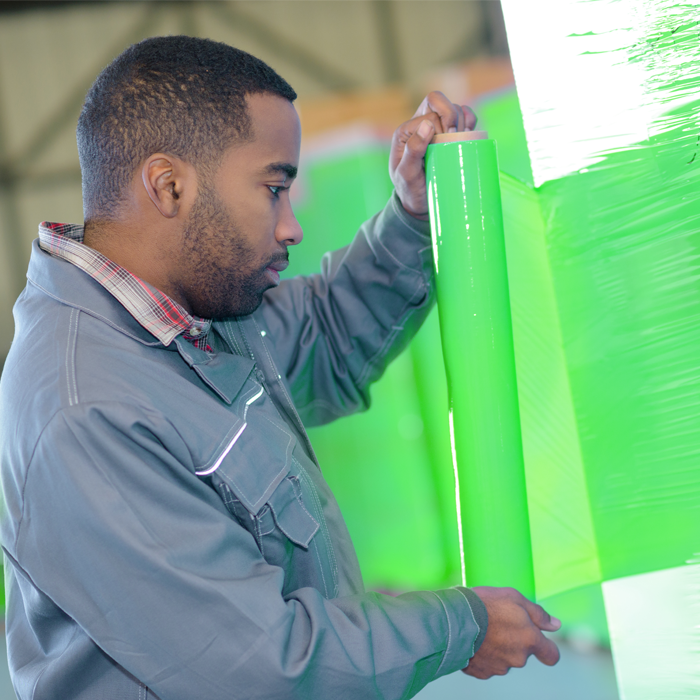 man in warehousing wrapping pallet by hand with green stretch wrap
