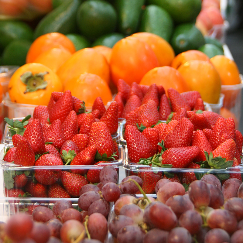 various fruits and vegetables packed in clear plastic trays in retail shelf for sale