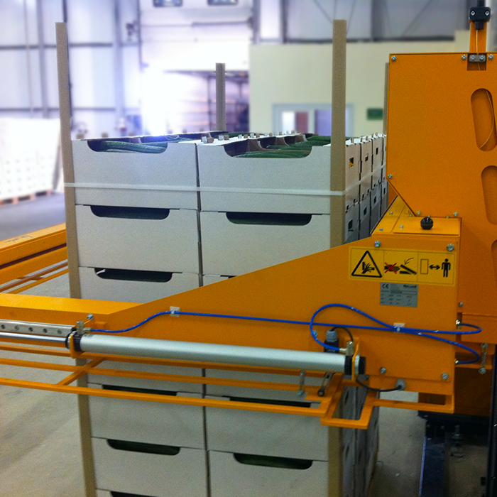 pallet of english cucumbers being secured by automatic strapping machine