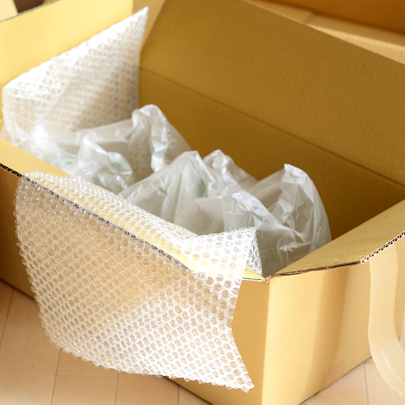 sheets of inflated bubble wrap inside cardboard box on the floor