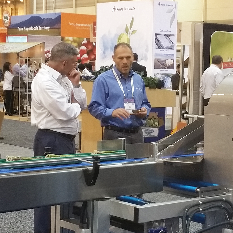 sam campson automation manager with visitor at pma booth in front of rgd flow wrap machine
