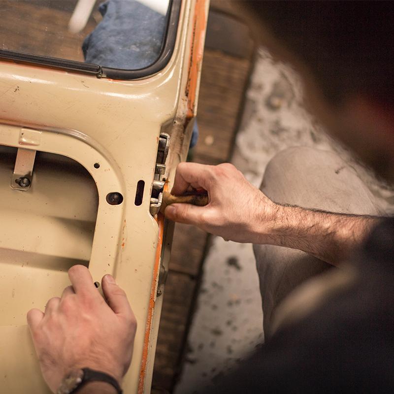 man adjusting car door part inside manufacturing facility