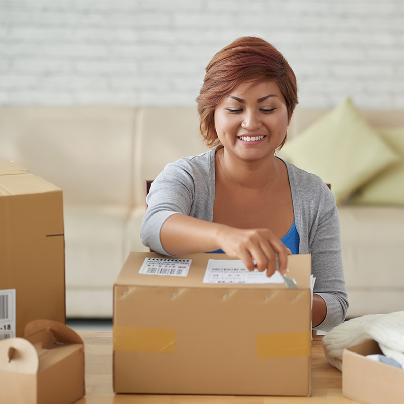 woman sitting in living room unboxing a cardboard parcel package using a knife