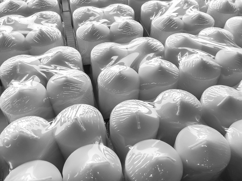 white candles wrapped in shrink wrap packaging packs of four
