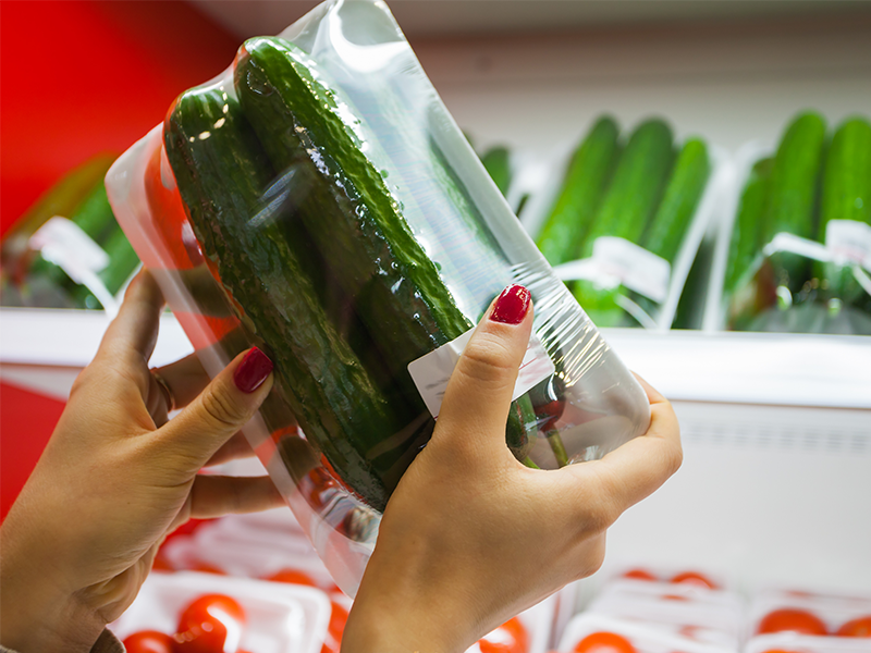 two cucumbers packed in plastic film on white foam tray in supermarket
