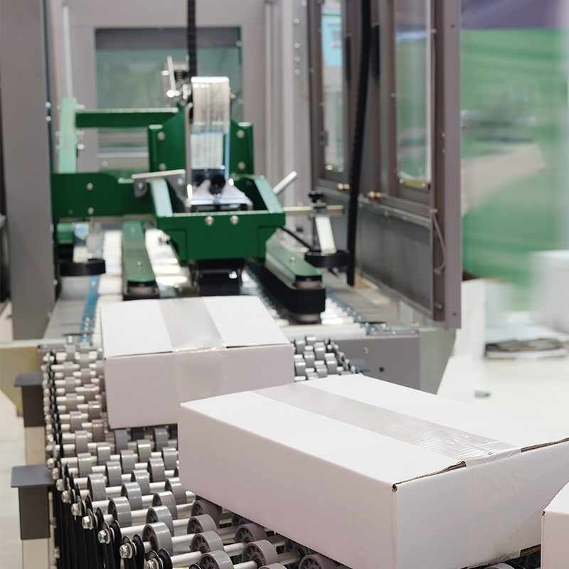 automatic case sealing machine sealing white corrugated cases with clear poly tape