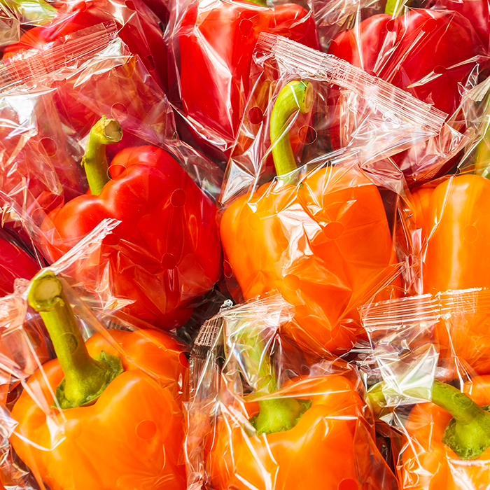 individually flow wrapped red and orange bell peppers on store shelf