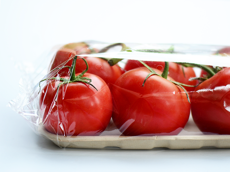 tomatoes on a tray wrapped in clear perforated flow wrap film