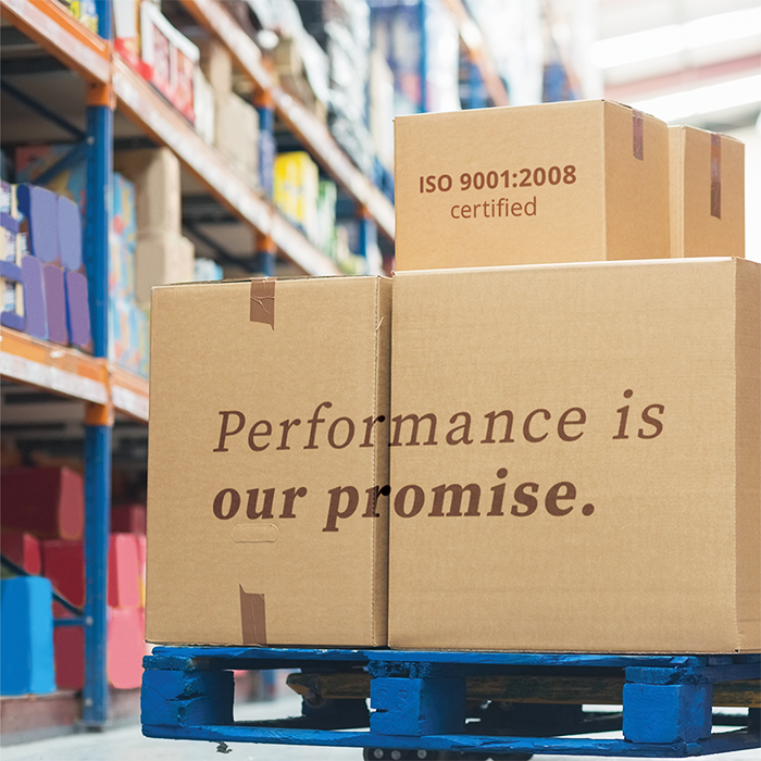 performance is our promise tagline on cardboard boxes in warehouse facility