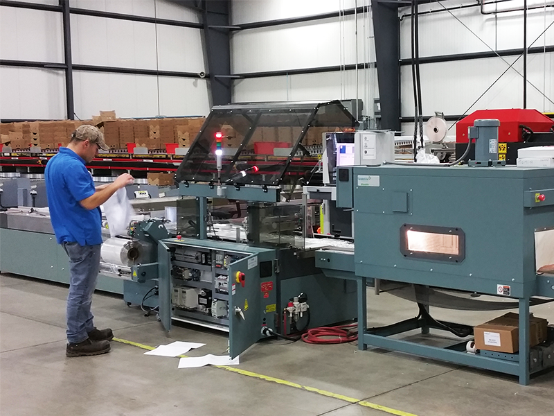 service technician installing shanklin triumph 2 shrink wrap machine at greenhouse grower facility